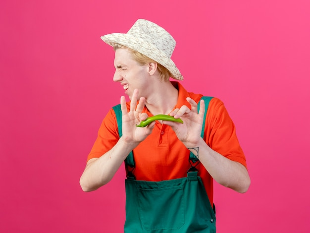 Young gardener man wearing jumpsuit and hat holding green chili pepper