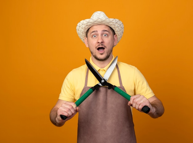Giovane giardiniere uomo che indossa tuta e cappello che tiene tagliasiepi stupito e sorpreso