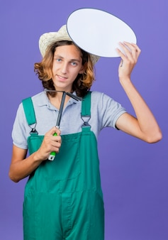 Young gardener man wearing jumpsuit and hat holding mattock and blank speech bubble