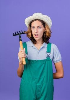 Young gardener man wearing jumpsuit and hat holding mini rake being surprised