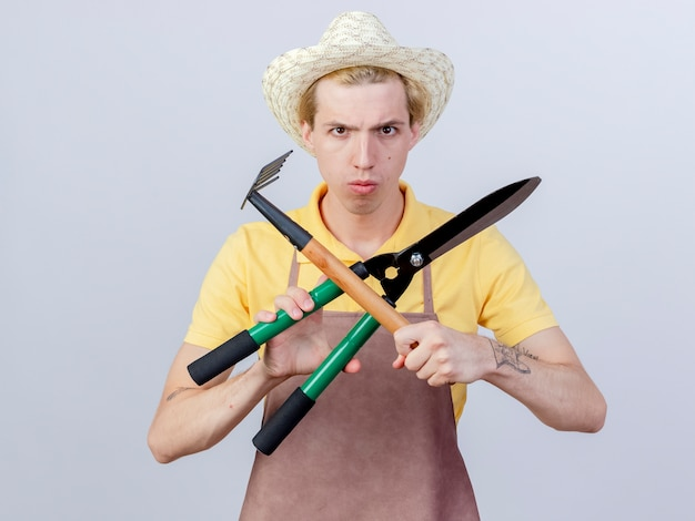 Giovane giardiniere che indossa tuta e cappello con mini rastrello e tagliasiepi incrociando le mani con una faccia seria