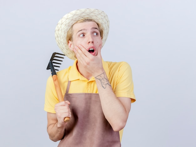 Young gardener man wearing jumpsuit and hat holding mini rake looking aside amazed and surprised
