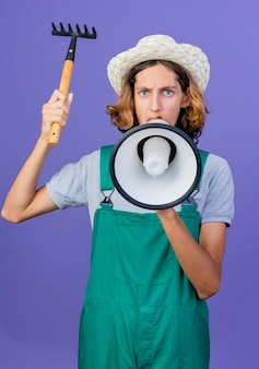 Young gardener man wearing jumpsuit and hat holding mini rake shouting