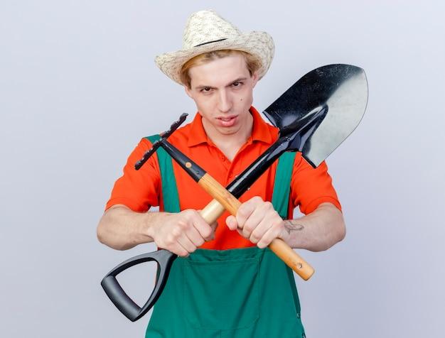 Giovane giardiniere uomo che indossa tuta e cappello azienda mini rastrello e pala guardando la telecamera con viso serio attraversando le mani in piedi su sfondo bianco