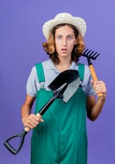 Giovane giardiniere uomo che indossa tuta e cappello che tiene mini rastrello e pala con faccia seria