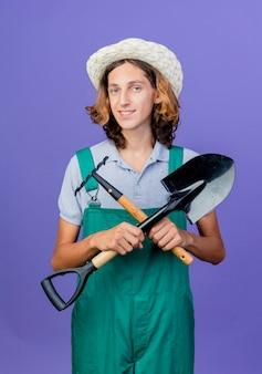 Giovane giardiniere uomo che indossa tuta e cappello che tiene mini rastrello e pala
