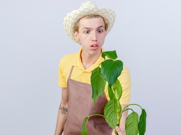 Giovane giardiniere che indossa tuta e cappello che tiene la pianta guardandola confusa
