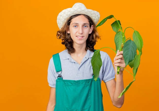 Young gardener man wearing jumpsuit and hat holding plant