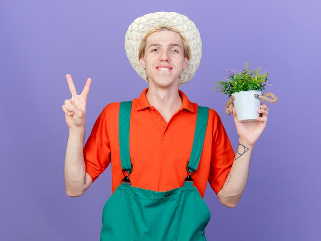 Young gardener man wearing jumpsuit and hat holding potted plant smiling