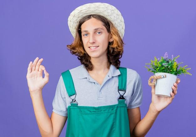 Giovane giardiniere uomo che indossa tuta e cappello che tiene pianta in vaso con il sorriso