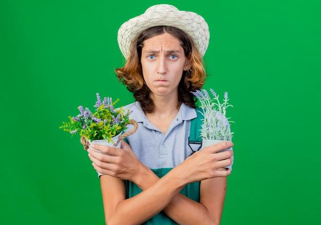 Giovane giardiniere uomo che indossa tuta e cappello che tiene piante in vaso con espressione triste