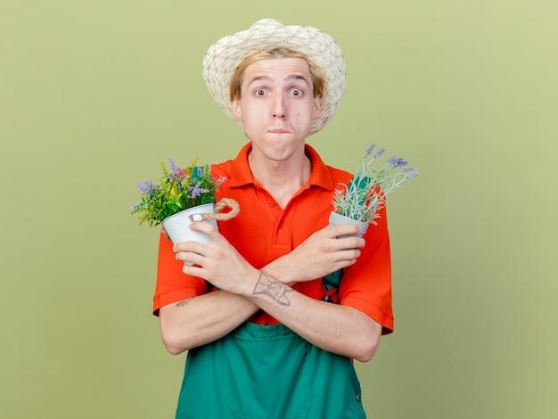 Giovane giardiniere uomo che indossa tuta e cappello tenendo le piante in vaso