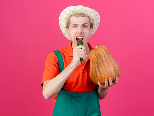Young gardener man wearing jumpsuit and hat holding pumpkin and cucumber