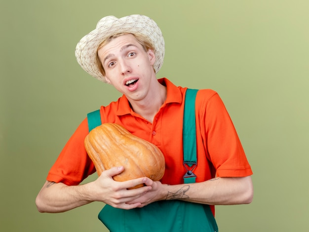 Young gardener man wearing jumpsuit and hat holding pumpkin