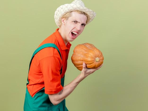 Giovane giardiniere uomo che indossa tuta e cappello tenendo la zucca