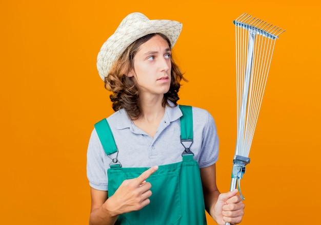 Giovane giardiniere uomo che indossa tuta e cappello tenendo il rastrello che punta con il dito indice