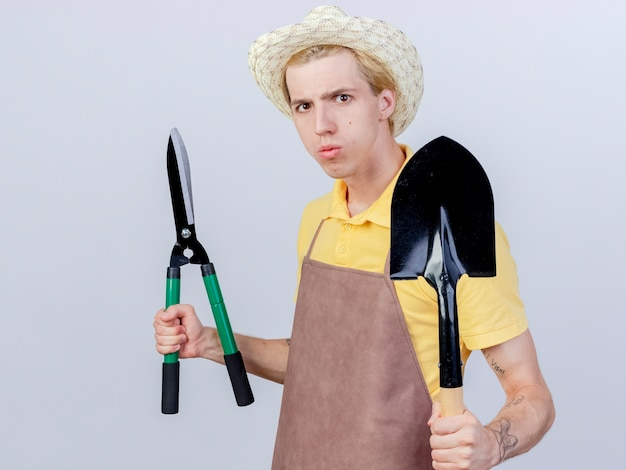 Young gardener man wearing jumpsuit and hat holding shovel and hedge clippers with serious face