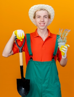 Giovane giardiniere uomo che indossa tuta e cappello tenendo la pala e pianta in vaso