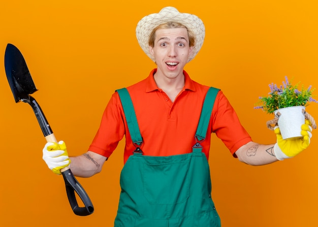 Young gardener man wearing jumpsuit and hat holding shovel showing potted plant smiling