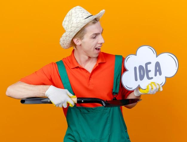 Giovane giardiniere uomo che indossa tuta e cappello tenendo la pala e il segno della bolla di discorso