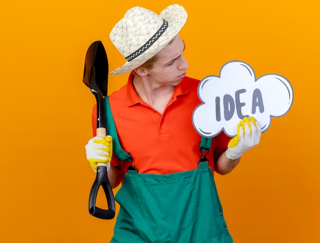 Young gardener man wearing jumpsuit and hat holding shovel and speech bubble sign