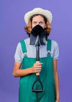 Giovane giardiniere uomo che indossa tuta e cappello tenendo la pala con la faccia seria