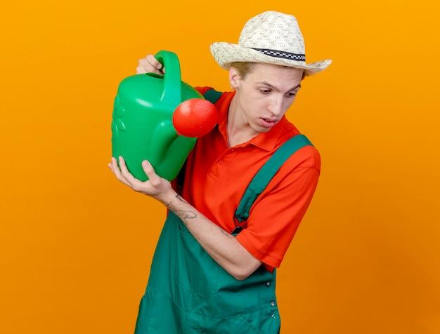 Giovane giardiniere uomo che indossa tuta e cappello tenendo annaffiatoio guardando la fotocamera con la faccia seria in piedi su sfondo arancione