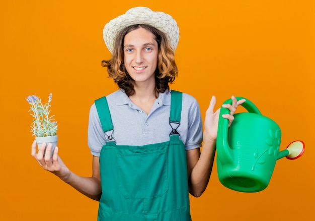 Young gardener man wearing jumpsuit and hat holding watering can and potted plant
