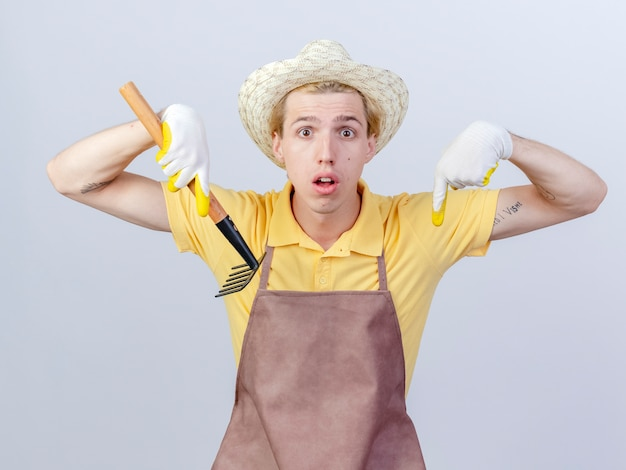 Young gardener man wearing jumpsuit and hat in rubber gloves holding mini rake being surprised pointing down
