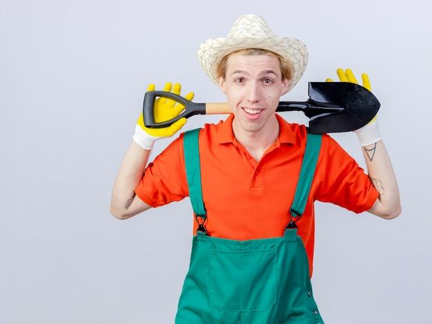 Giovane giardiniere uomo che indossa tuta e cappello in guanti di gomma tenendo la pala guardando la telecamera sorridendo allegramente in piedi su sfondo bianco