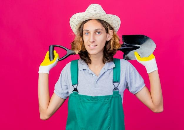 Giovane giardiniere uomo che indossa tuta e cappello indossando guanti di gomma tenendo la pala