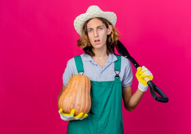 Young gardener man wearing jumpsuit and hat wearing rubber gloves holding shovel