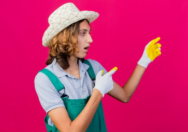 Young gardener man wearing jumpsuit and hat wearing rubber gloves pointing