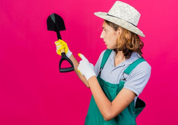 Giovane giardiniere uomo che indossa tuta e cappello che indossa guanti di gomma