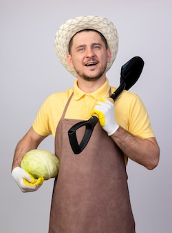 Giovane giardiniere uomo che indossa tuta e cappello in guanti da lavoro tenendo il cavolo e la pala guardando la parte anteriore con il sorriso sul viso in piedi sopra il muro bianco