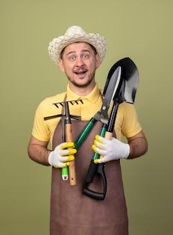 Giovane giardiniere uomo che indossa tuta e cappello in guanti da lavoro in possesso di attrezzature da giardinaggio guardando davanti sorridente con la faccia felice in piedi sopra la parete leggera