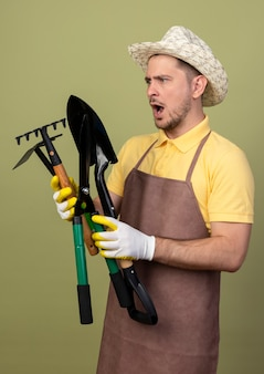 Young gardener man wearing jumpsuit and hat in working gloves holding gardening equipments looking at them confused and surprised