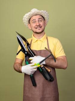 Young gardener man wearing jumpsuit and hat in working gloves holding gardening equipments with smile on face