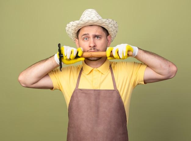 Giovane giardiniere uomo che indossa tuta e cappello in guanti da lavoro tenendo mini rastrello sul viso guardando la parte anteriore con faccia seria in piedi sopra la parete leggera