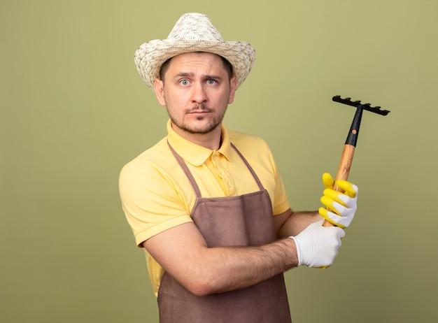 Giovane giardiniere uomo che indossa tuta e cappello in guanti da lavoro che tiene mini lookign rastrello in telecamera con faccia seria