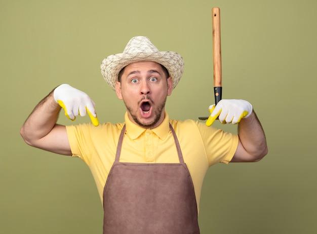 Giovane giardiniere uomo che indossa tuta e cappello in guanti da lavoro tenendo mini rastrello guardando davanti sorpreso che punta con le dita indice verso il basso in piedi sopra la parete leggera