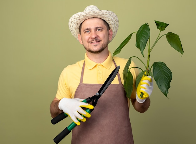 Giovane giardiniere uomo che indossa tuta e cappello in guanti da lavoro che tengono pianta e tagliasiepi guardando la parte anteriore con il sorriso sul viso in piedi sopra la parete leggera