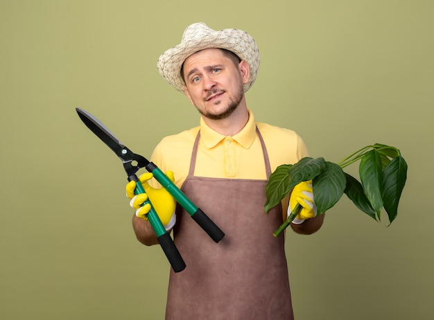 Young gardener man wearing jumpsuit and hat in working gloves holding plant and hedge clippers smiling with happy face