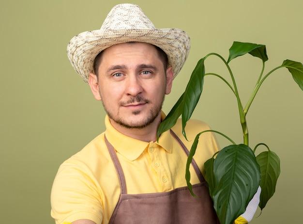 Giovane giardiniere uomo che indossa tuta e cappello in guanti da lavoro tenendo la pianta guardando la parte anteriore con il sorriso sul viso in piedi sopra la parete chiara