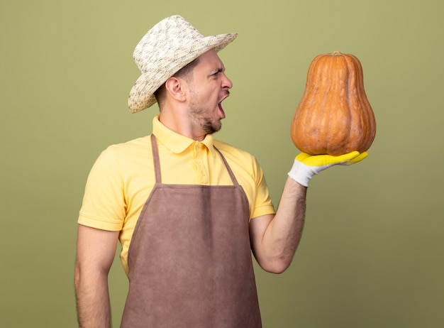 Giovane giardiniere uomo che indossa tuta e cappello in guanti da lavoro tenendo la zucca guardandolo con la faccia arrabbiata in piedi sopra la parete chiara
