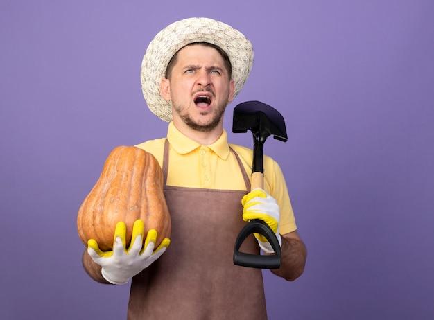 Giovane giardiniere uomo che indossa tuta e cappello in guanti da lavoro tenendo la zucca e la pala guardando confuso e scontento in piedi sopra la parete viola