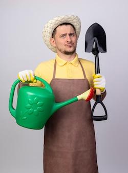 Giovane giardiniere uomo che indossa tuta e cappello in guanti da lavoro che tengono annaffiatoio e pala essendo confuso