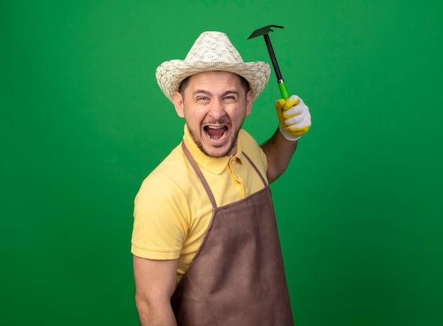 Giovane giardiniere uomo che indossa tuta e cappello in guanti da lavoro oscillante mattock gridando con espressione aggressiva