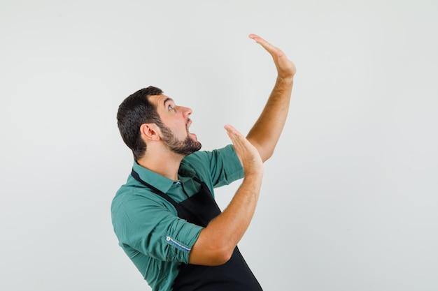Молодой садовник, защищаясь, поднимает руки в футболке, фартуке и выглядит испуганным. передний план.