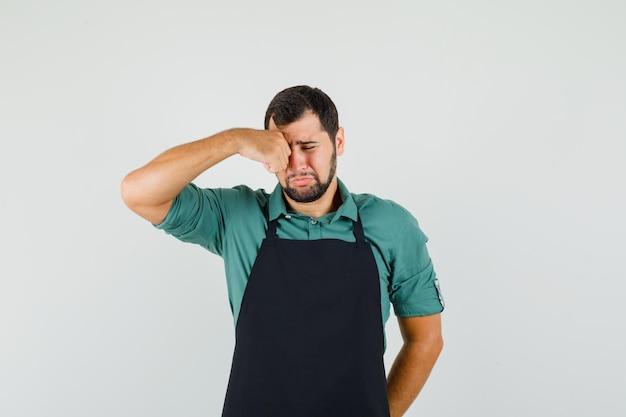 Giovane giardiniere che si sfrega gli occhi mentre piange in maglietta, grembiule e sembra triste. vista frontale.